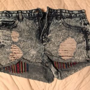 A pair of distressed acid washed jean shorts.